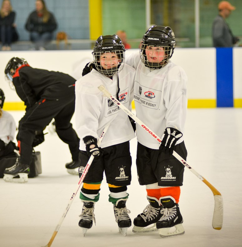 two young hockey players arms around each other